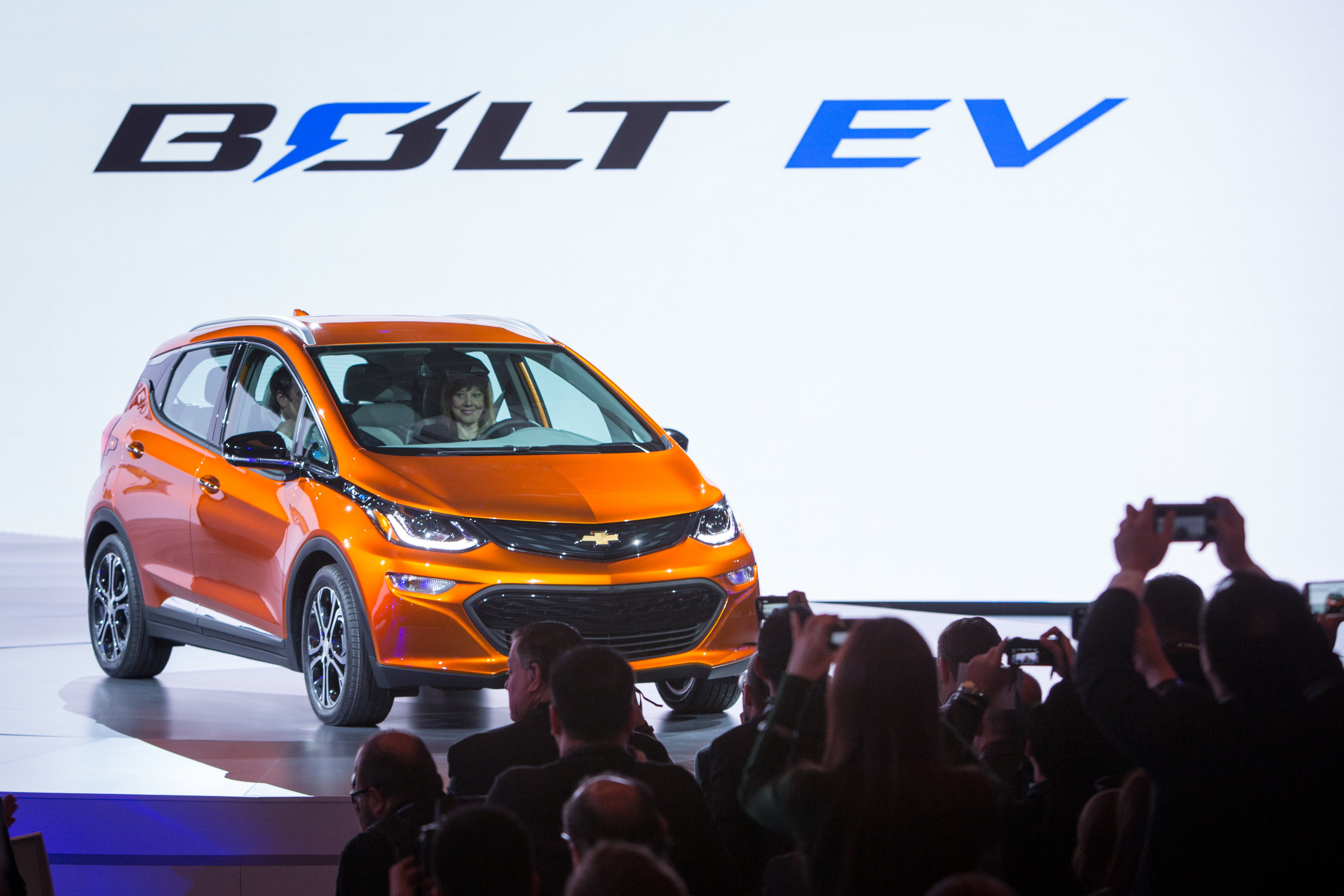 General Motors Chairman and CEO Mary Barra drives the 2017 Chevrolet Bolt EV onto the stage Monday, January 11, 2016 at the North American International Auto Show in Detroit, Michigan. GM Executive Vice President Product Development Mark Reuss rides in the passenger seat. The Bolt EV offers more than 200 miles of range on a full charge at a price below $30,000 after Federal tax credits. (Photo by Jeffrey Sauger for Chevrolet)